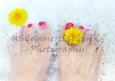 Middle Aged Woman's feet soaking with a Dandelion