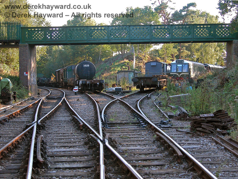This view west shows the track layout under the western footbridge more clearly. The main Groombridge sidings are on the right, with an additional siding to the left formed out of the Up line from Birchden. The operational line to Birchden (and eventually Eridge) is on the far left. 19.09.2005