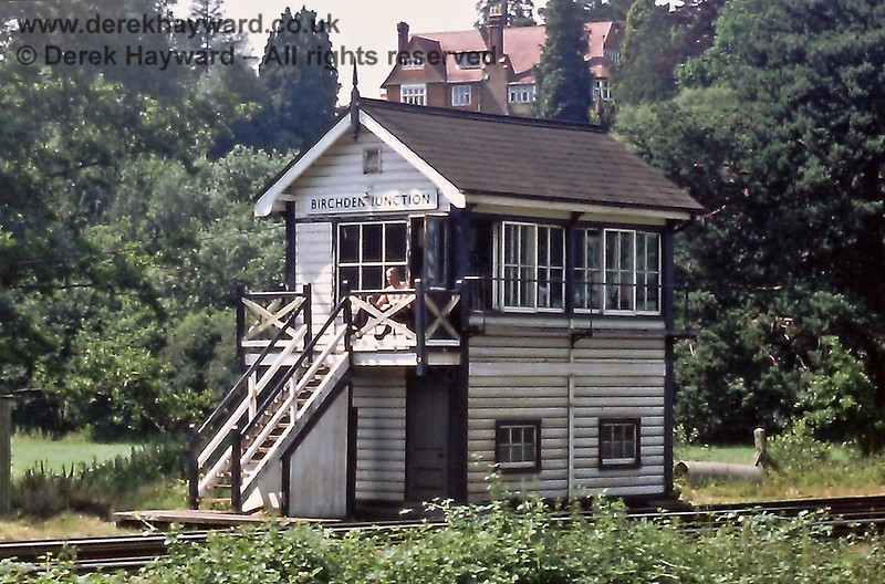 """Birchden Junction signal box on  06.07.1985, and the surveillance team hiding in the bushes catch the signalman working on his sun tan between trains.  The house revealed above the signal box is """"Glen Andred"""", a fine home built in 1867 and designed by architect Norman Shaw.  Shaw also (amongst other things) designed the 1887 Scotland Yard buildings, which are now used by the UK Parliament. Eric Kemp retains all rights to this image."""
