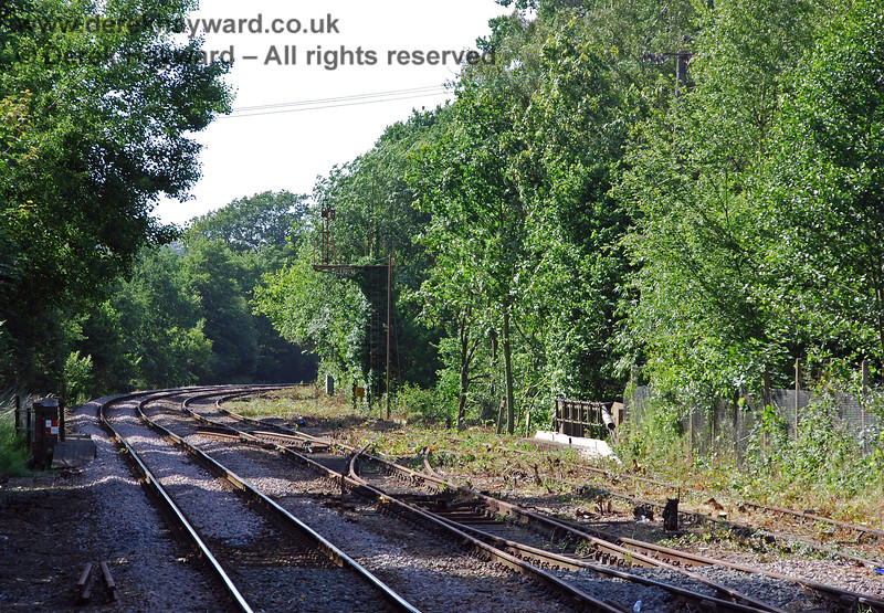 Looking north from Platform 1 at Eridge with a long lens. The Network Rail line is on the left, the Spa Valley Railway running line is in the centre of the picture and the SVR long siding on the right. Contractors were concentrating on bringing the SVR running line up to standard and cutting back the undergrowth. No work had been done on the track in the siding at the time. 22.06.2008