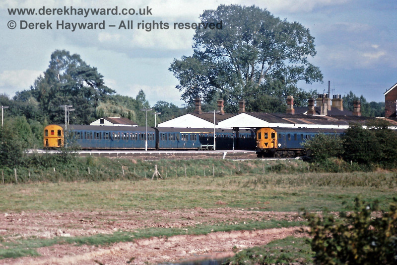 Looking across the fields to Eridge Station on Sunday 21.09.1975, with 3D unit 1315 on the 15:58 Tonbridge to Uckfield service (Platform 3) and 3H unit 1106 in Platform 1 waiting to leave at 16:33 with a Victoria train.    Eric Kemp retains all rights to this image.