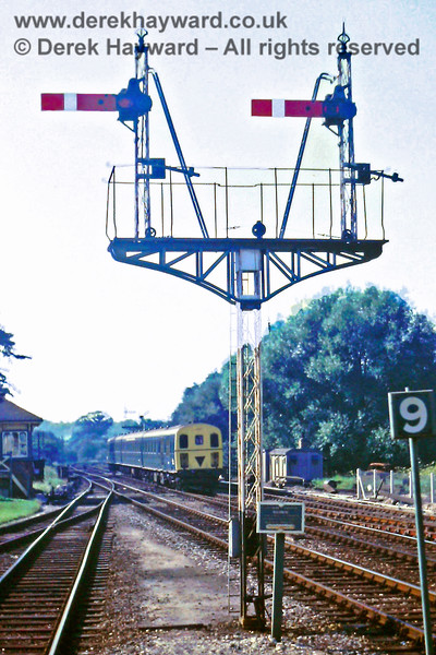 """The Up Starting signals at Eridge,  with 1307 arriving in the background on a southbound service.  The """"9"""" on the right is the marker showing where nine coach trains should stop, and thus indicating the rough length of the platforms at the time. 17.08.1971.  Eric Kemp retains all rights to this image."""