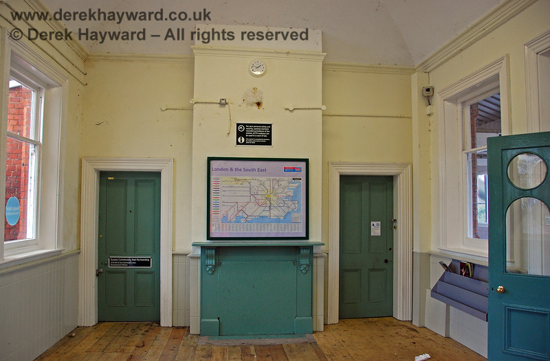 The interior of the booking hall, looking west, showing the old fireplace, and the more modern CCTV. It would have looked better if they had made good after the removal of the clock.  The office on the left was used by the Sussex Community Rail Partnership, Uckfield and East Grinstead Lines Development Officer.  Unfortunately there were few leaflets available on the racks, which was unusual. 28.01.2008