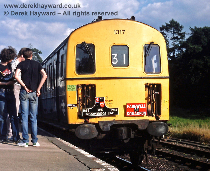"""Eridge on Saturday 06.07.1985, the last day of operation via Groombridge. 1317 and 1311 are waiting to depart with the 17:59 to Tunbridge Wells Central, the front of the unit carrying appropriate headboards.  Sadly the """"Save the Eridge Line"""" sticker had been ineffective, but the line would be partially re-born as the Spa Valley Railway.  Eric Kemp retains all rights to this image."""