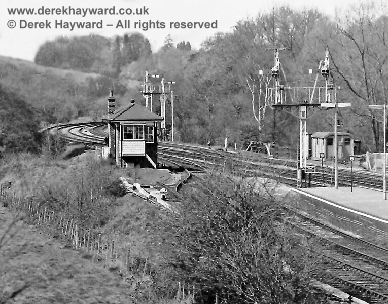 """The northern end of Eridge Station pictured on Sunday 20.04.1975.  The tracks nearest the camera are the line through Platform 1, and the adjacent Up siding, the escape from which was regulated by a ground signal and a sand drag running right up to the signal box (unintentional use of this sand drag was liable to upset the signalman).  The two Starting signals are at the end of the Up platforms, with the """"6"""" and """"9"""" stopping markers just beneath (you """"budged up"""" very slightly if you had nine coaches).  Beyond the signal box are the Down Home signals for Platforms 3 and 4, and hidden behind the bracket there is just a glimpse of the northbound Advance Starting signal, with Distant signals beneath it for the two routes at Birchden Junction.  The track furthest from the camera (east side of the line) is the """"long siding"""" and this image clearly shows it continuing around the bend.  Eric Kemp retains all rights to this image."""
