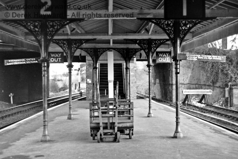 A bit of nostalgia.  The Up platform at Eridge on Saturday 29.11.1975, looking towards the footbridge.  The destination boards tell the story of the service that then existed, the Up siding buffers are on the right and the Down Starting signal can be glimpsed through the arch.  At the time there was a Royal Mail parcels chute under the footbridge steps (out of shot) and the empty barrows stand ready for the mail and parcels.  A lost era...    Eric Kemp retains all rights to this image.