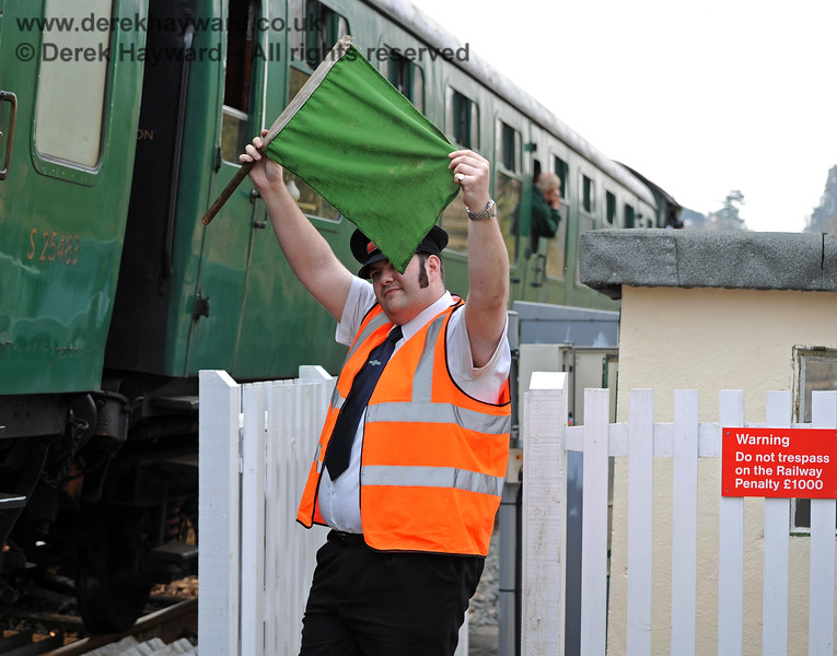 As part of the agreement for the safe operation of Forge Farm Crossing, a Crossing Keeper (Gate Attendant) is provided, here displaying a green flag. If the users can cope with 60mph Network Rail trains passing through I struggle with the concept that 25mph heritage trains have to come to a stand in advance of the crossing. 250311 10422