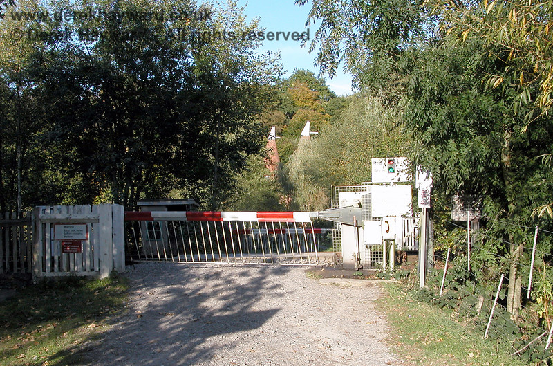"""Forge Farm Crossing viewed from the west side.  The Network Rail """"traffic light"""" system can be seen to the right of the closed barrier. By default the gates at this type of crossing are kept closed, and are opened by authorised users who rely on the red and green lights to ascertain if a train is coming.  There are different rules for large vehicles.  05.10.2003"""