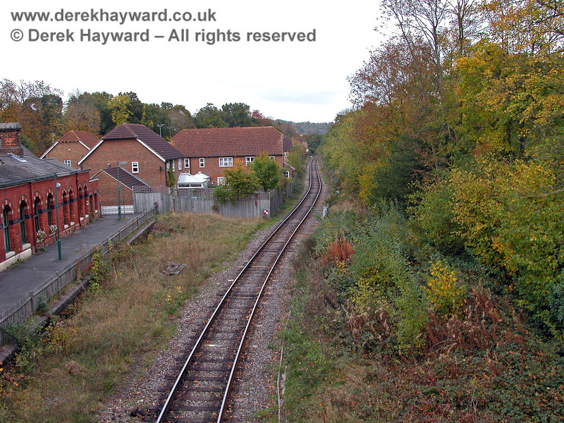 At the eastern end of Groombridge Station building development was permitted on the trackbed. With hindsight this was perhaps an unfortunate decision. This view east shows the single track threading it's way behind the development in 2003.  The line of the old platform is clear, and the right hand side of the picture shows heavy undergrowth. 19.10.2003