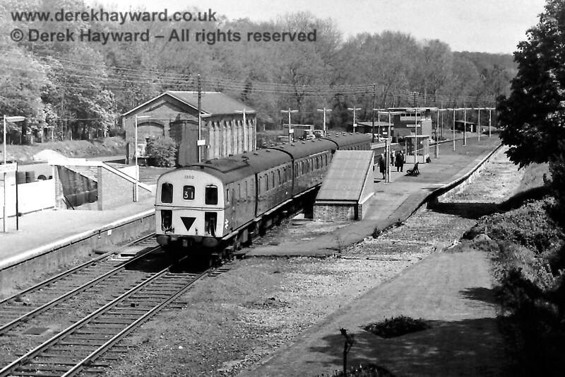 1302 leaves the main line side of what was once an island platform at Groombridge on Saturday 03.05.1975.  The train is the 11:58 from Tonbridge to Eridge .  The bushes are flourishing outside the disused door to the goods shed.  Eric Kemp retains all rights to this image.