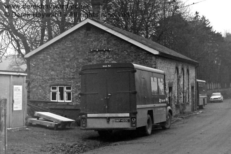 """A somewhat drab winter's day at Groombridge on 30.12.1969.   The notice on the concrete building on the left proclaims """"Closure of Goods Yard"""", and the building beyond it was, by then, in departmental use (hence the presence of two British Rail vans).  Eric Kemp retains all rights to this image."""