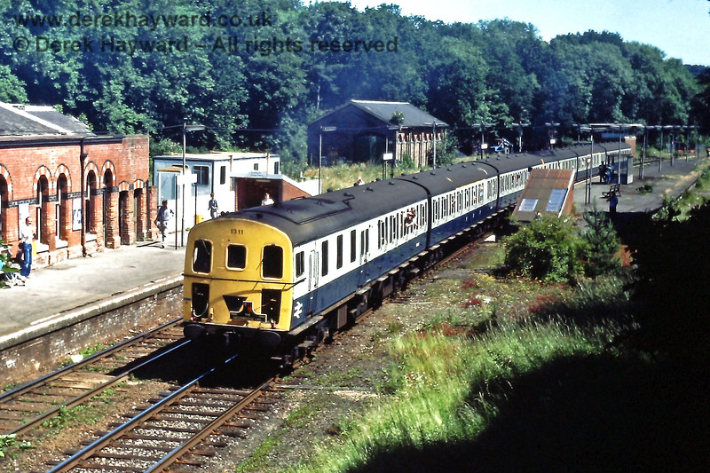 It's the last day of services on the line (06.07.1985) but trains could not run to and from Tonbridge owing to engineering work.  1311 and 1317 are at Groombridge on the 11:20 from Tunbridge Wells Central.  The former westbound loop is already looking overgrown but a single line on roughly the same alignment would be re-born as the Spa Valley Railway.  Eric Kemp retains all rights to this image.