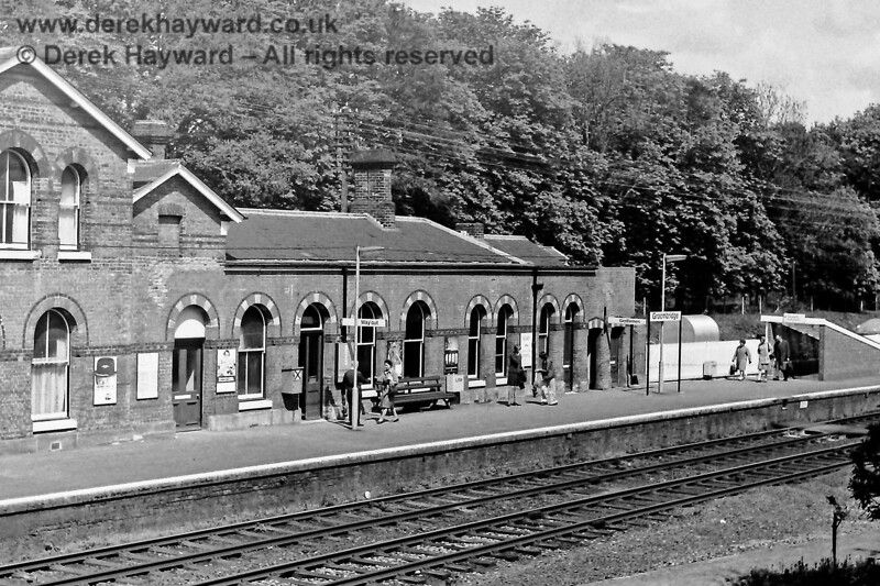The eastern end of Groombridge station building, bereft of canopies, on 03.05.1975.  Passengers are making their way from the subway towards the exit, where a porter awaits to collect their tickets.  Eric Kemp retains all rights to this image.