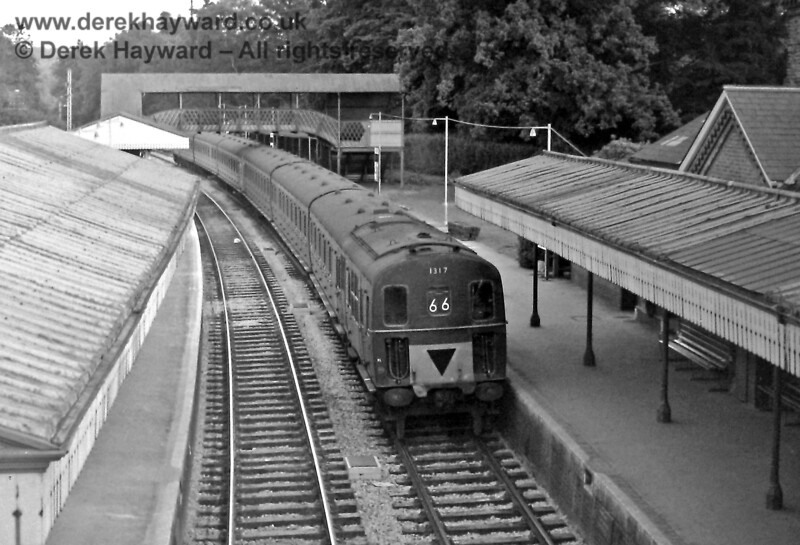 1317, in green livery, leads 1305 (blue) through Lingfield on the 20:05 empty coaching stock working from East Grinstead on Thursday 17.07.1969.  Part of the footbridge in the background was later used at Sheffield Park on the Bluebell Railway.   Eric Kemp retains all rights to this image.