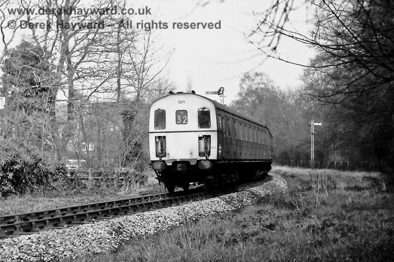 1311 heading away from Grove Junction with the 12:58 Tonbridge to Uckfield service.  Note the distant signal heavily offset to the right of the photo to improve sighting on the curve.  Sunday 23.02.1975.  Eric Kemp retains all rights to this image.