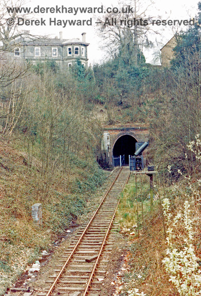 Grove Tunnel western portal pictured after closure in 1985.  The gate in the fence is open and the arms have been removed from the semaphore signal adjacent to the portal.  The rear of the colour light signal is open and presumably components have been removed.  Nick Mander retains all rights to this image.