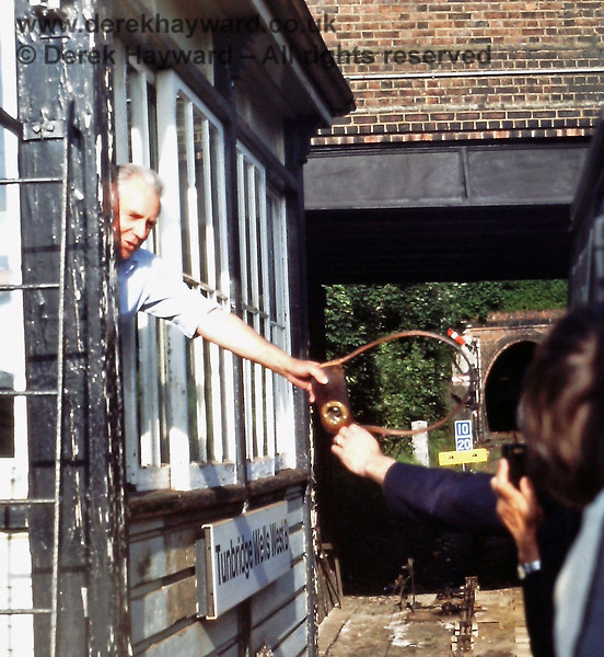 On the last day of service, Saturday 06.07.1985, the driver collects the single line token from the signalman at Tunbridge Wells West 'B' signal box.  Eric Kemp retains all rights to this image.