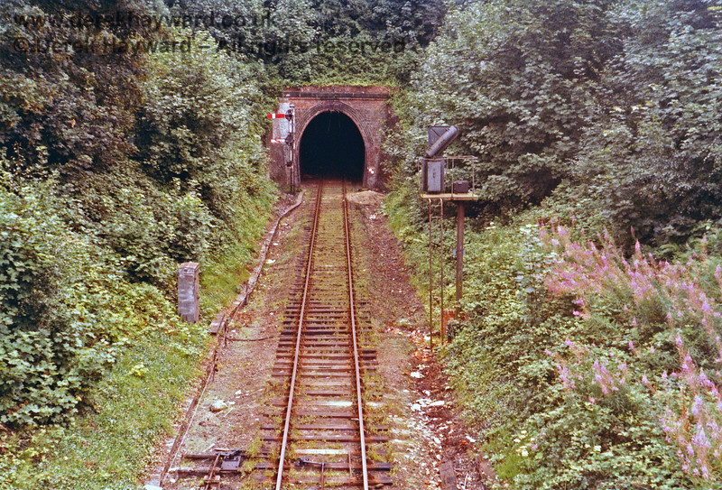 Grove Tunnel western portal pictured just before closure in 1985.  Weeds are growing on the track and the undergrowth has not been cut for a while.  Nick Mander retains all rights to this image.