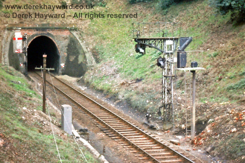 """A new colour light signal being installed to replace the low slung semaphore signals at the eastern end of Tunbridge Wells West in March 1976.  The signals were so positioned in order that they could be sighted from Grove Tunnel. The picture also catches the  eastbound semaphore (Advance Starter) together with the """"Shunt"""" arm which allowed shunting moves to proceed ahead into the tunnel. Eric Kemp retains all rights to this image."""