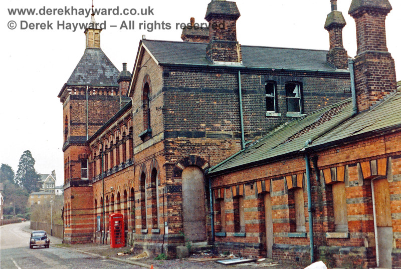 Tunbridge Wells West Station, pictured shortly after closure in 1985.  Note that the ground floor is boarded up and the windows on the upper floor are broken.  However, someone has stopped their Morris Minor and is using the telephone box. Nick Mander retains all rights to this image.