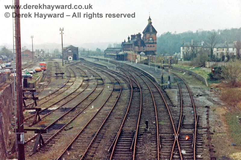 Tunbridge Wells West Station, pictured shortly after closure in 1985.  The arms have gone from the signals and the whole area looks very sad.  An orange traffic cone rests in the track leading to the bay platform (Platform 2).  Nick Mander retains all rights to this image.