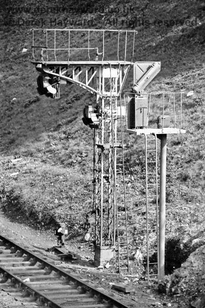 A new colour light signal being installed to replace the low slung semaphore signals at the eastern end of Tunbridge Wells West in April 1976.  The signals were so positioned in order that they could be sighted from Grove Tunnel.  Eric Kemp retains all rights to this image.