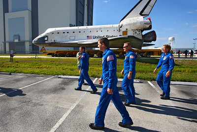 The crew of the final shuttle mission walk alongside Atlantis.