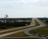 This is the road the track vehicle that moved the Space Shuttle to the launch pad followed, you can see how wide the crawler was when compares to the road that runs beside it. Pad 39A, that Shuttles launched from is to the left