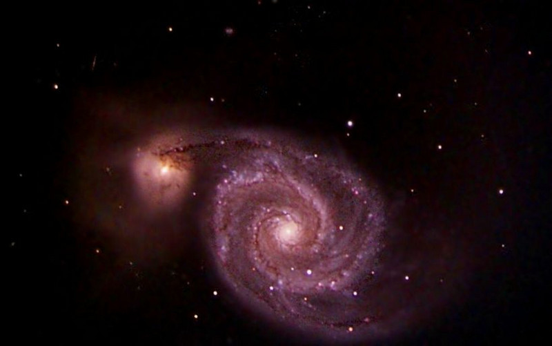 M51: The Whirlpool Galaxy is a classic spiral galaxy. At only 23 million light years distant and fully 65 thousand light years across, M51, also known as NGC 5194, is one of the brightest and most picturesque galaxies on the sky. The smaller galaxy appearing here above and to the left is well behind M51, as can be inferred by the dust in a foreground spiral arm blocking light from this smaller galaxy. The Whirlpool, pictured above, is visible with binoculars in the constellation of Canes Venaciti. M51 is a spiral galaxy of type Sc and is the dominant member of a whole group of galaxies. Astronomers speculate that M51's spiral structure is primarily due to its gravitational interaction with this smaller galaxy.