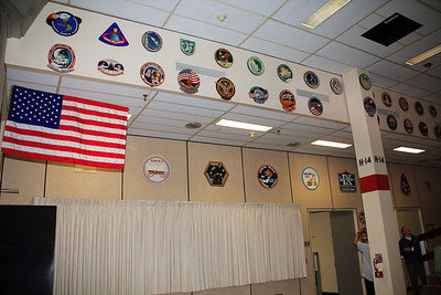 """Each control room has the patches from each of it's missions on the wall. Near the top here, you can see the patches for Apollo 11 and Apollo 13, a couple of the more famous missions. The flag on the left has actually been to the moon. I was told that it was used as a """"backup flag"""", and never left the lunar module, but it did make the trip."""