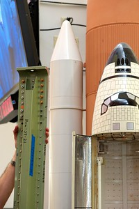 02/23/2011 - A piece of reinforced stringer hardware is held up against a model space shuttle in the Kennedy Space Center news center.