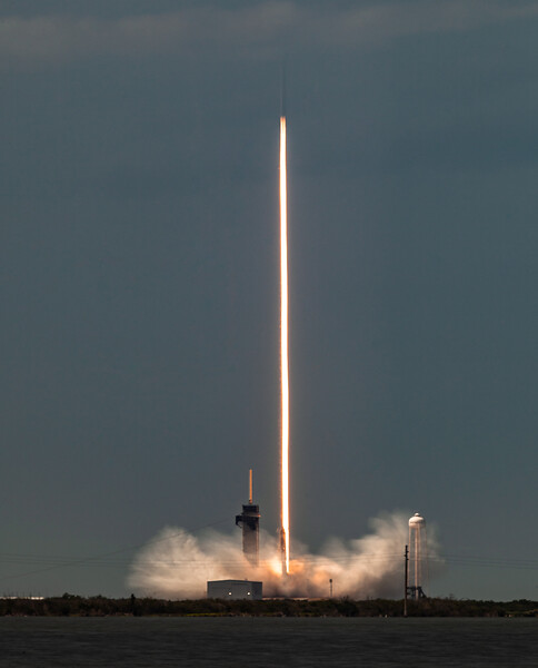 """May 30th, 2020 - An historic flight for NASA, SpaceX and the US Space Program. After nine year, NASA sends two astronauts to low earth orbit from US soil using, for the very first time, a private rocket and capsule.  This is a long exposure photo of the SpaceX's Falcon 9 rocket carrying into orbit NASA Astronauts Doug Hurley and Bob Behnken onboard a CrewDragon Capsule towards the International Space Station.   The long exposure produces the effect of a """"light beam"""" or laser beam effect from the engines of the rocket during the first seconds of lift-off.  Please contact me directly if you need a commercial license. Thank you."""