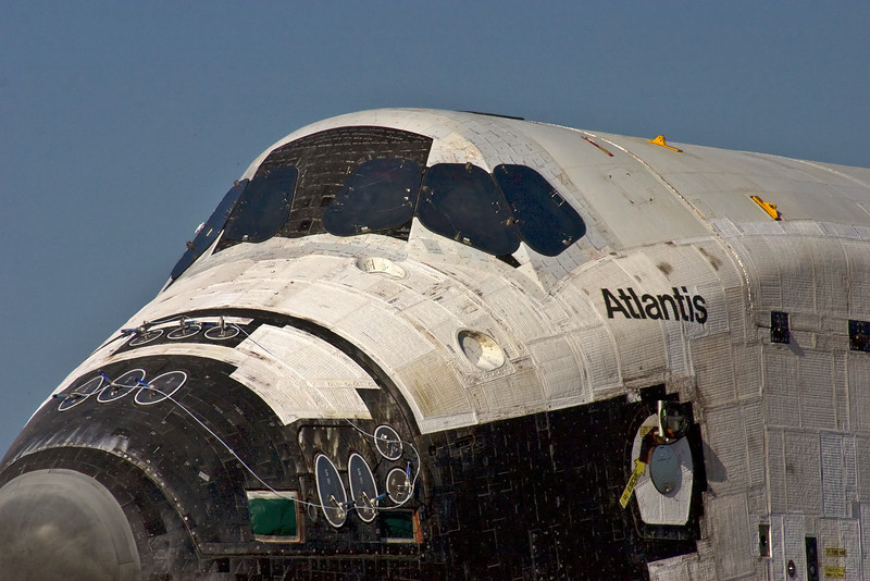A close-up shot of the nose section of Space Shuttle Atlantis against azure blue skies.