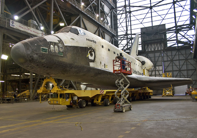 Atlantis waits in the Transfer Aisle of the massive Vehicle Assembly Building before she is mated to the waiting External Fuel Tank and Solid Rocket Boosters. This same spot saw huge Saturn V rockets stacked for the Apollo Program.