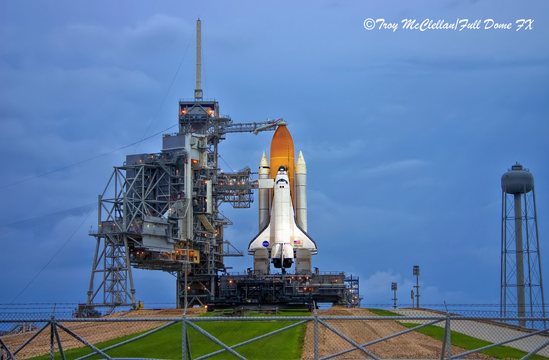 Atlantis waits under gloomy skies on the evening before the last shuttle launch and the end of an era.