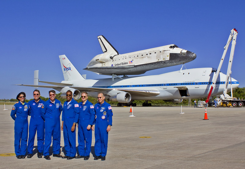 Discovery's final crew poses in front of her the day before she leaves KSC.