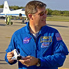 STS-133 Mission Specialist Steve Bowen looks toward Discovery while holding a diecast space shuttle model.