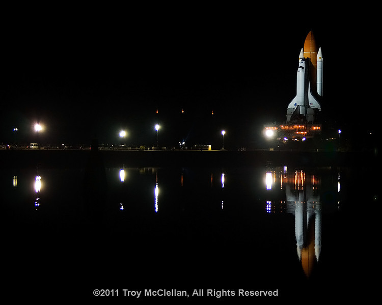 Discovery and reflecting in the water as seen from the Press Site at KSC.