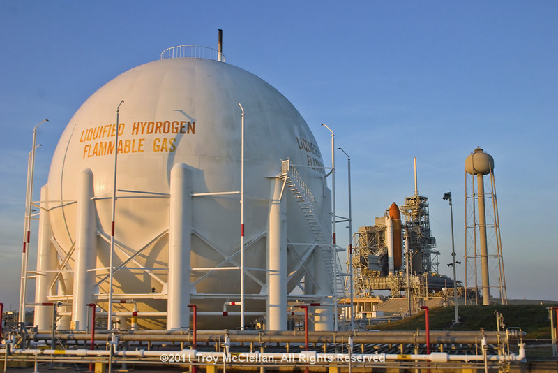Liquid hydrogen storage tank with Discovery in the background just a few minutes after sunrise.
