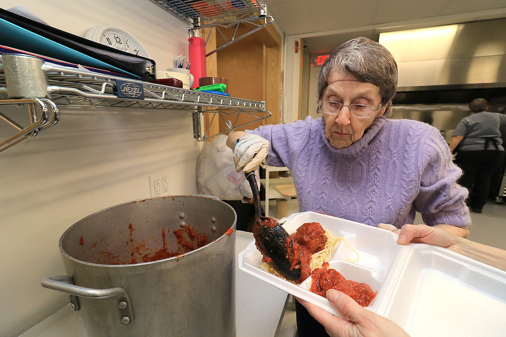 . Rollstone Congregational Church in Fitchburg holds a a spaghetti dinner on the second Wednesday of every month as a fundraiser for the church. It is put on by the kitchen committee from the church. Carolyn Barney puts some sauce and meatballs on a to go plate during the dinner. SENTINEL & ENTERPRISE/JOHN LOVE