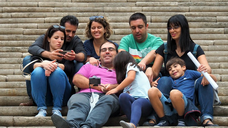 A family enjoying a selfie portrait on the steps of the cathedral in Girona, Costa Brava