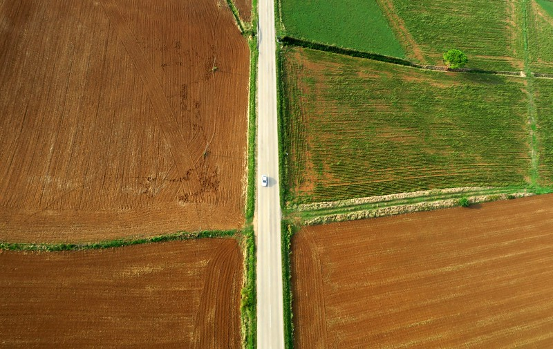 An overhead perspective shot of a car driving in a rural area