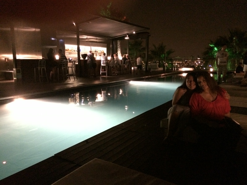 Linds and Avi with backdrop of pool, bar, and lights of Barcelona!(oops pardon my finger got in the way😁)