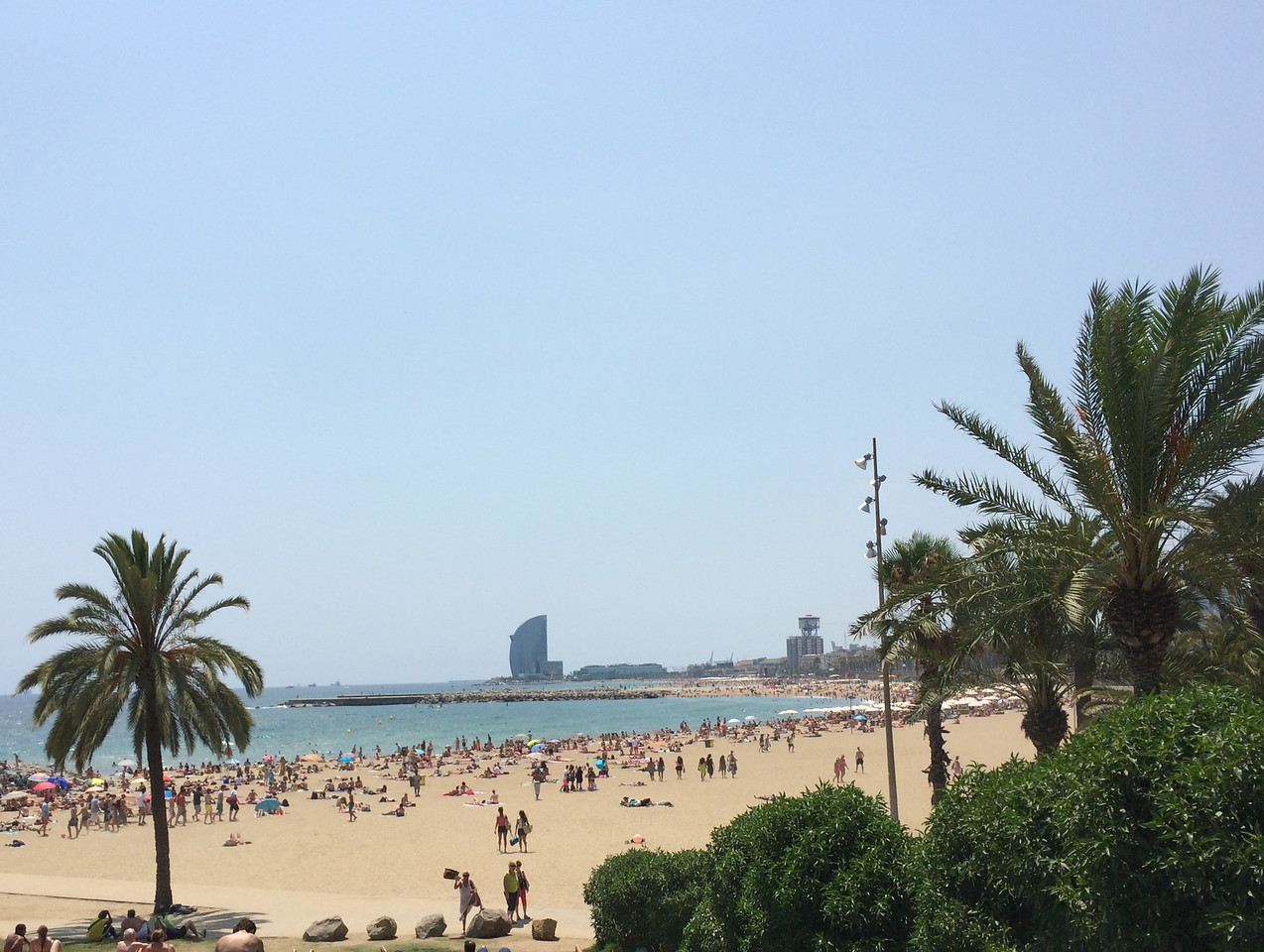 The crowded Barceloneta Beach on the Mediterranean with the W hotel sticking out in the distance.