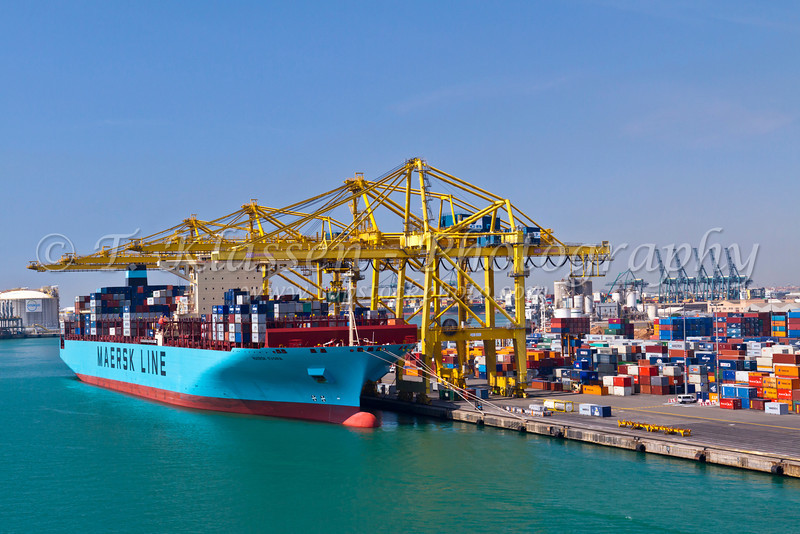 A cargo container ship loading and unloading at the port of Barcelona, Spain.