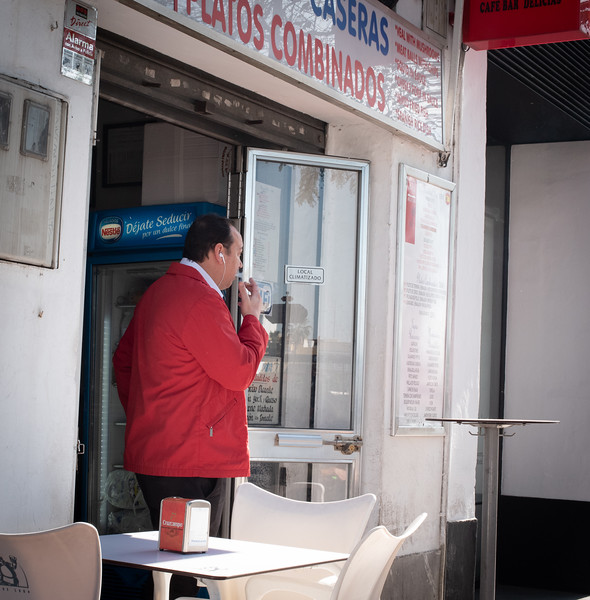 My morning coffee bar and a man in a red jacket smoking a cigarette.