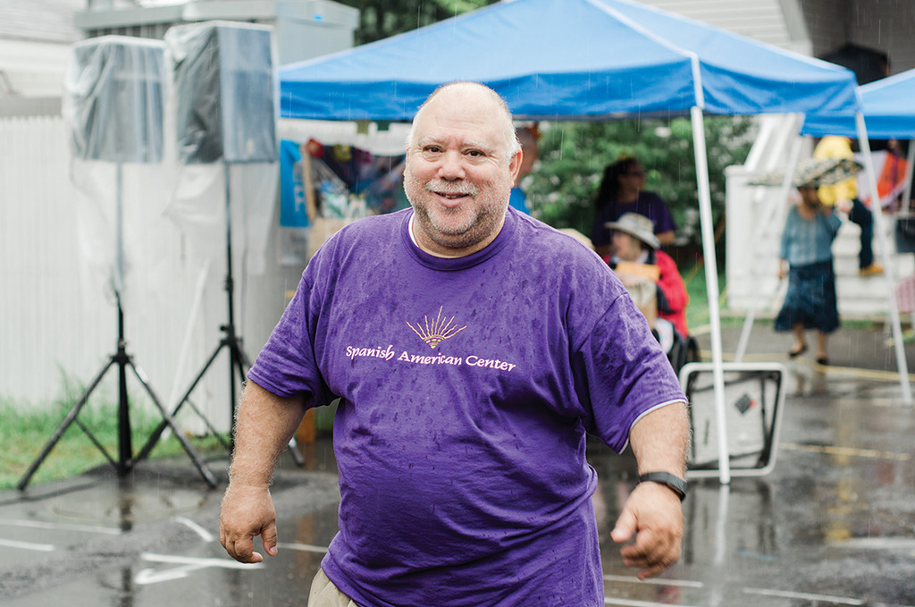 . Mickey Guzman ventures out into the rain the Spanish American Center\'s 50th anniversary block party on Saturday, August 5, 2017. SENTINEL & ENTERPRISE / Ashley Green