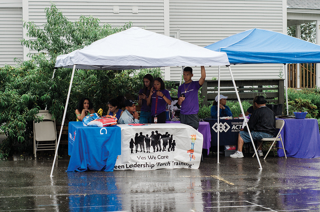 . Guests huddle together under tents during a downpour at the Spanish American Center\'s 50th anniversary block party on Saturday, August 5, 2017. SENTINEL & ENTERPRISE / Ashley Green