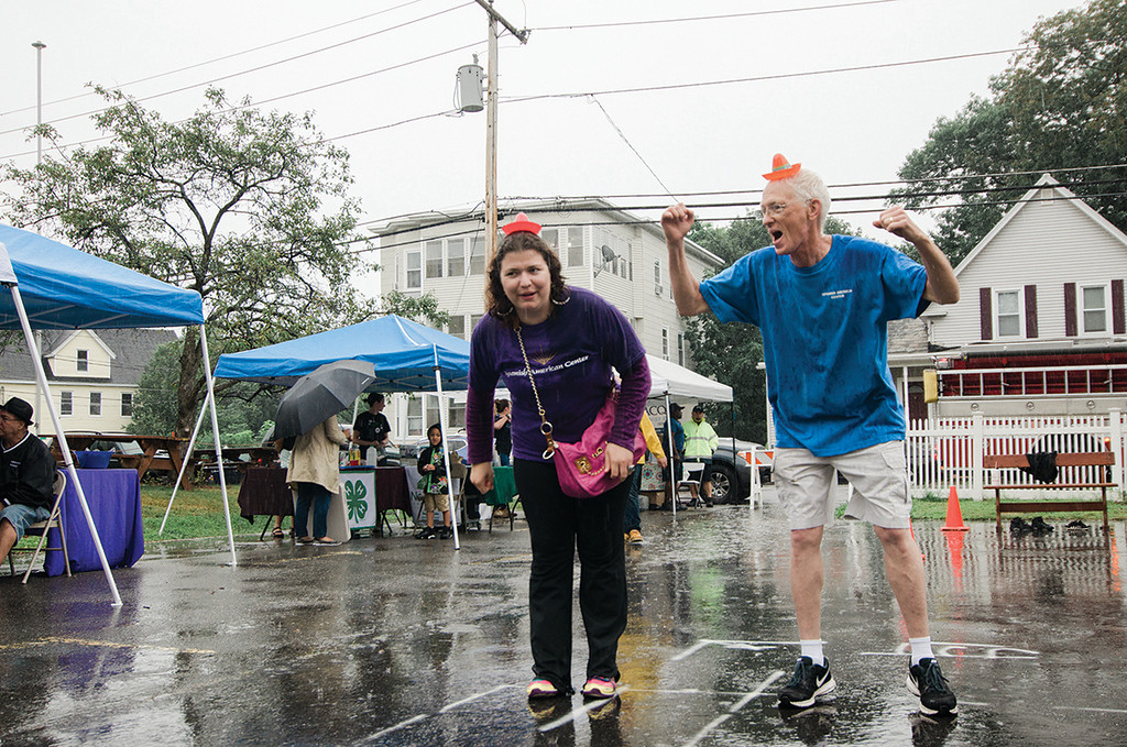 . Jean-Pierre Boissy and Crystal Guyette dance in the rain during the Spanish American Center\'s 50th anniversary block party on Saturday, August 5, 2017. SENTINEL & ENTERPRISE / Ashley Green