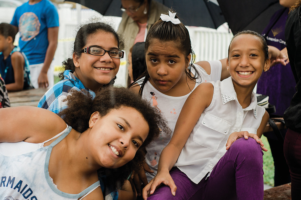 . Isabella Bible, Yanina Cambero, Keirianys Campos and Kariam Campos huddle together to stay dry during a downpour at the Spanish American Center\'s 50th anniversary block party on Saturday, August 5, 2017. SENTINEL & ENTERPRISE / Ashley Green